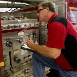 man checking fire apparatus equipment
