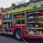 Red and neon yellow custom fire truck sits on the road with the storage compartments open.