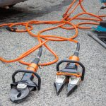 Two hydraulic rescue tools, shears and a spreader, on the ground