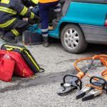 Hydraulic rescue tools on the ground next to a car