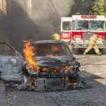 burning car in front of a firetruck